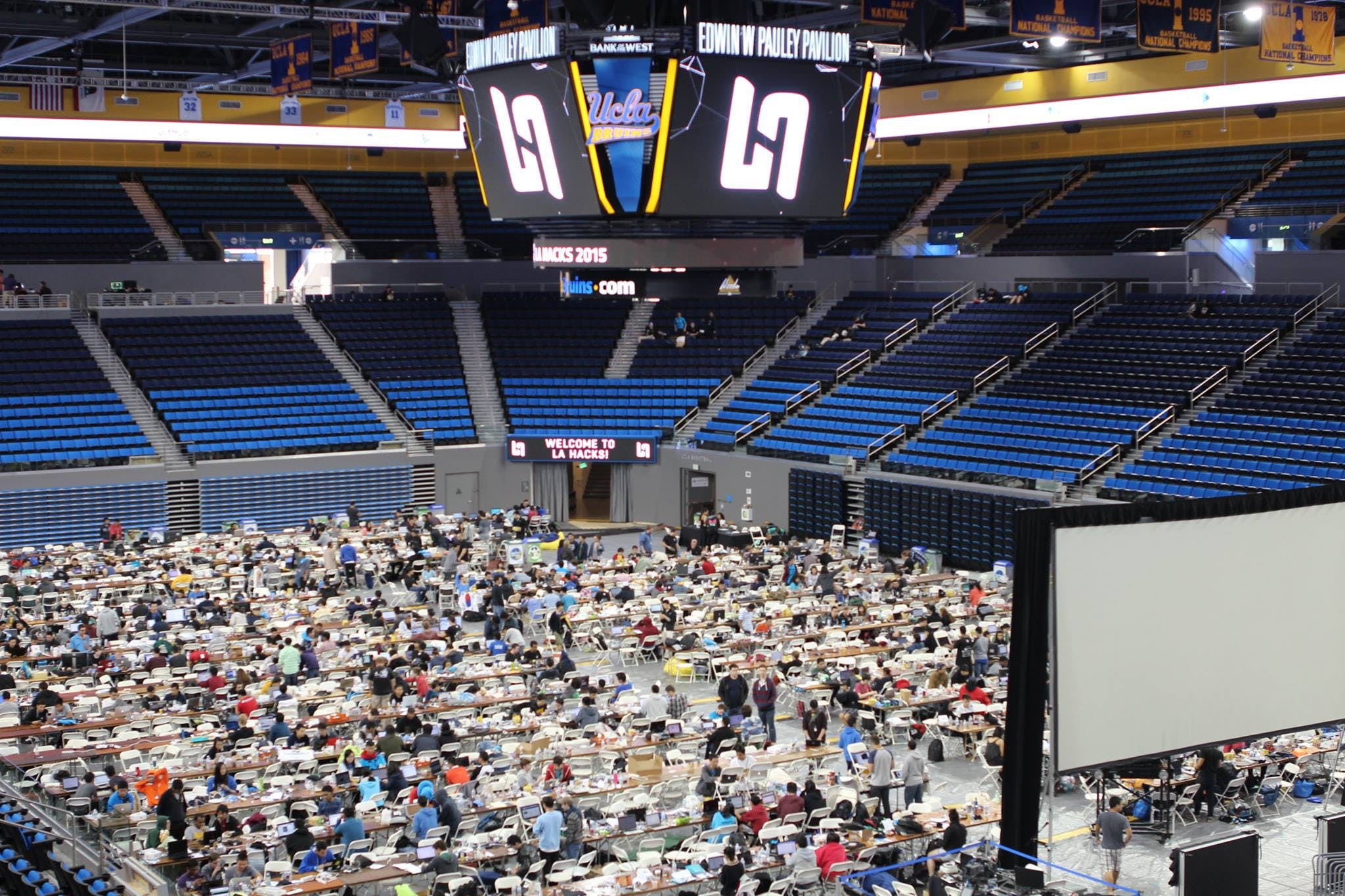 Stadium is filled with rows of tables and students using computers.