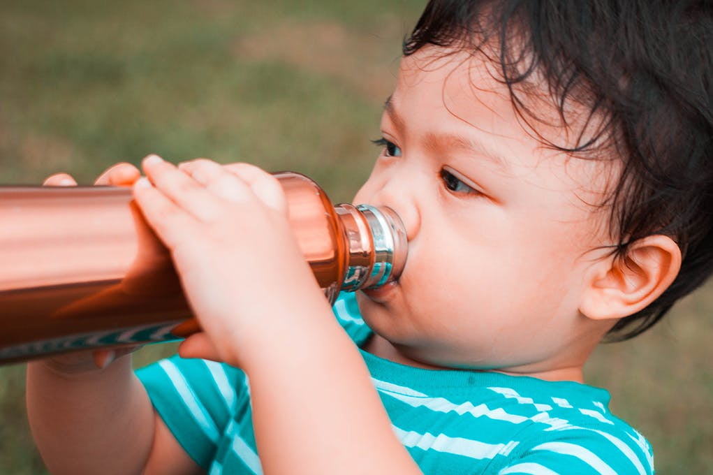 A toddler drinks water from a reusable bottle