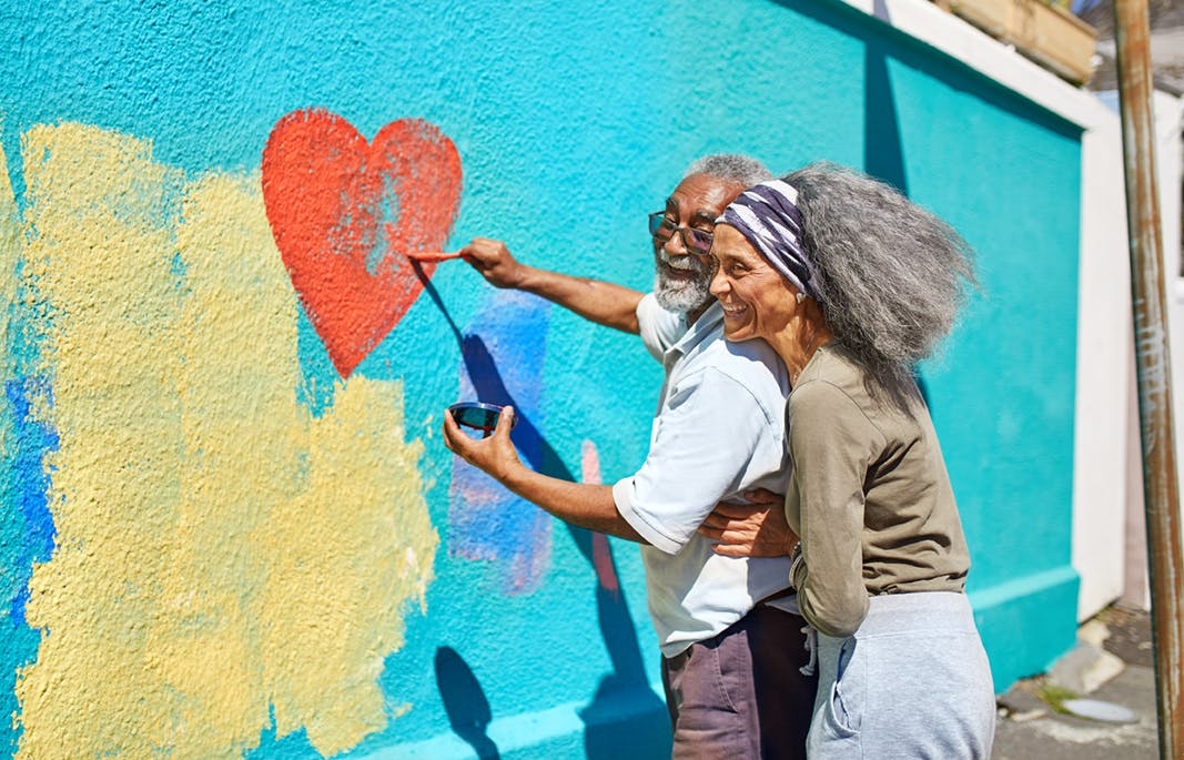 An elderly couple paint a mural together.