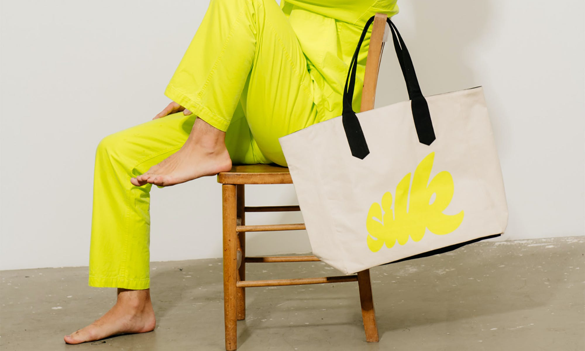 Model in yellow outfit, holding a bag that says silk