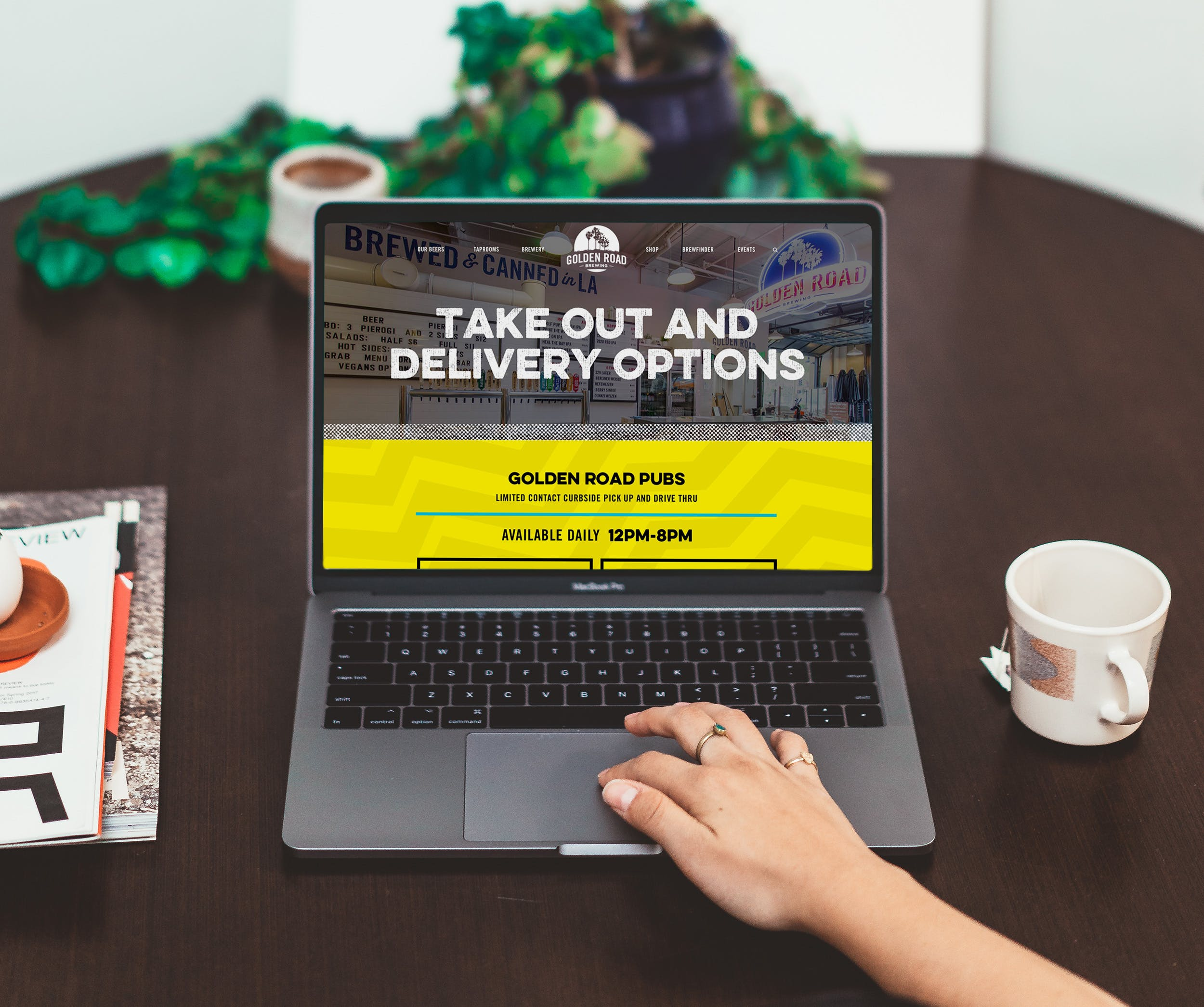 A hand is on the scroll pad of a laptop with the Golden Road homepage. There is a coffee mug to the right of the laptop. A plant in the background.