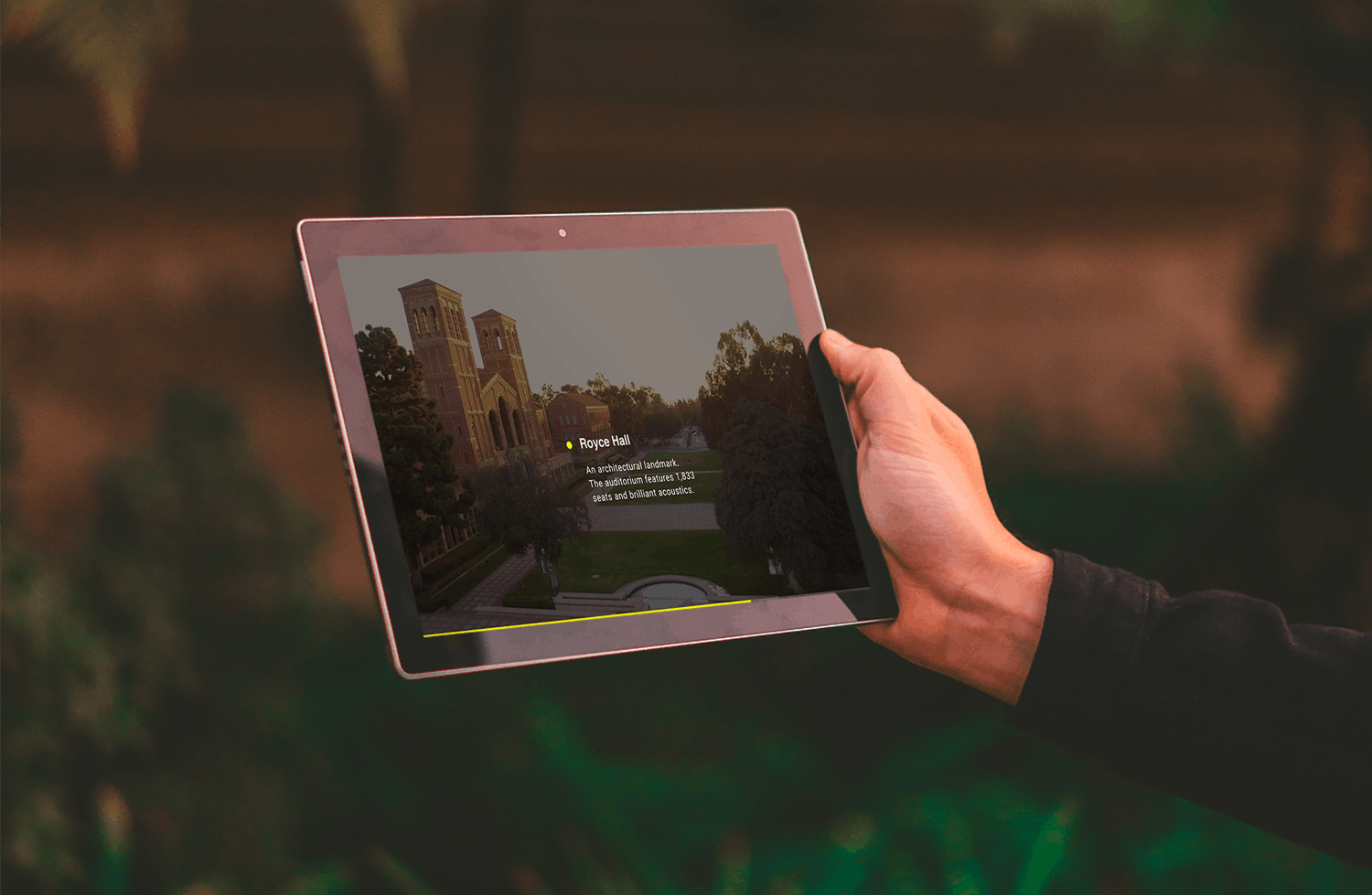 A hand holds an iPad with grass blurred out behind the iPad. The UCLA campus is shown on the iPad.