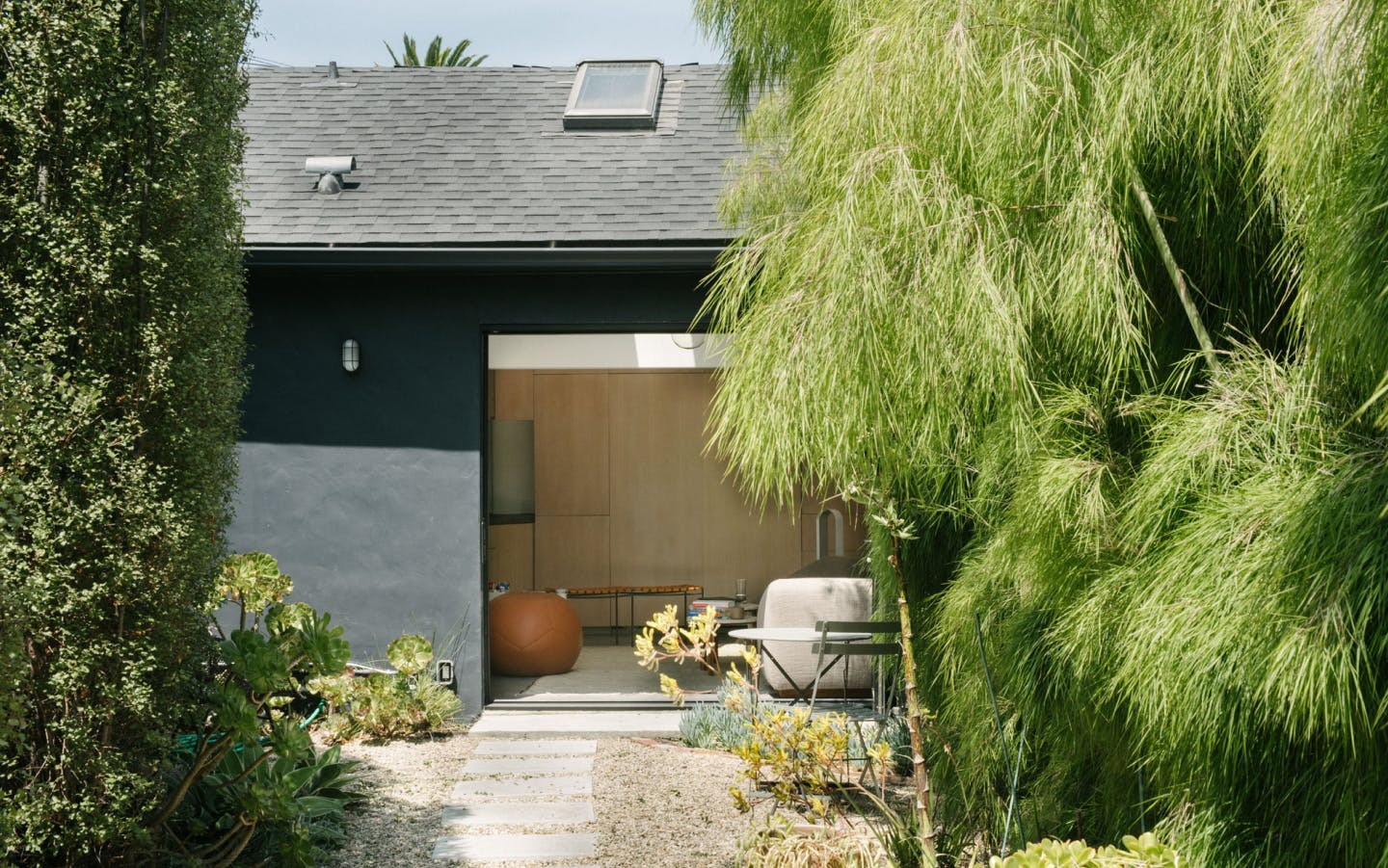 The outside of a bungalow in Venice Beach. There are trees in the foreground and a black bungalow with a large garage door open. Inside you can see two stools and a leather beanbag chair. In the foreground there's also a little bistro table set