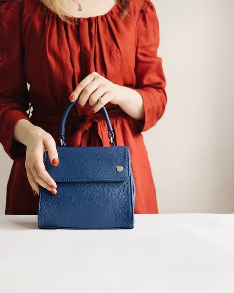 woman holding blue leather bag