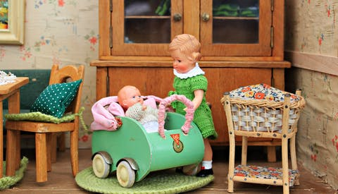 Girl and infant doll inside doll house