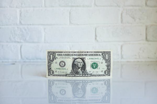 photo of one dollar bill in front of white brick wall