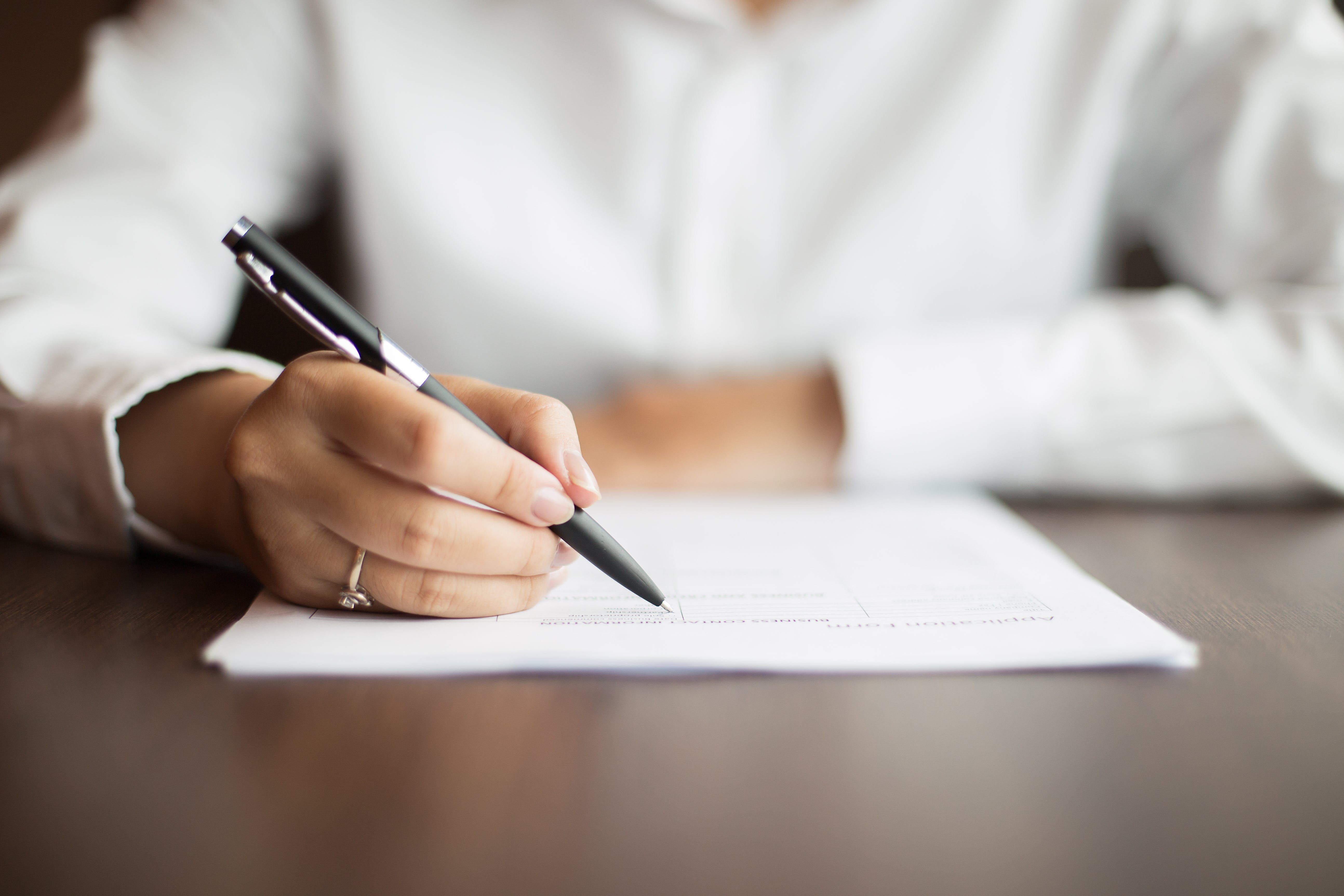 woman sitting to sign an escrow agreement