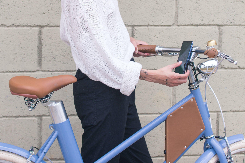 Vela 2 conectada com aplicativo - Uma mulher mexendo no aplicativo da Vela antes de pedalar sua bicicleta elétrica.