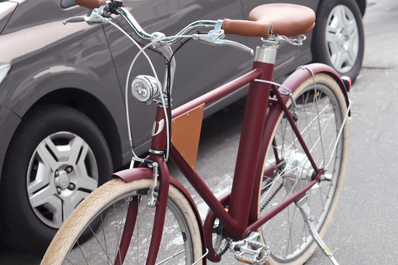 Bicicleta Vela vinho em frente a carro popular cinza