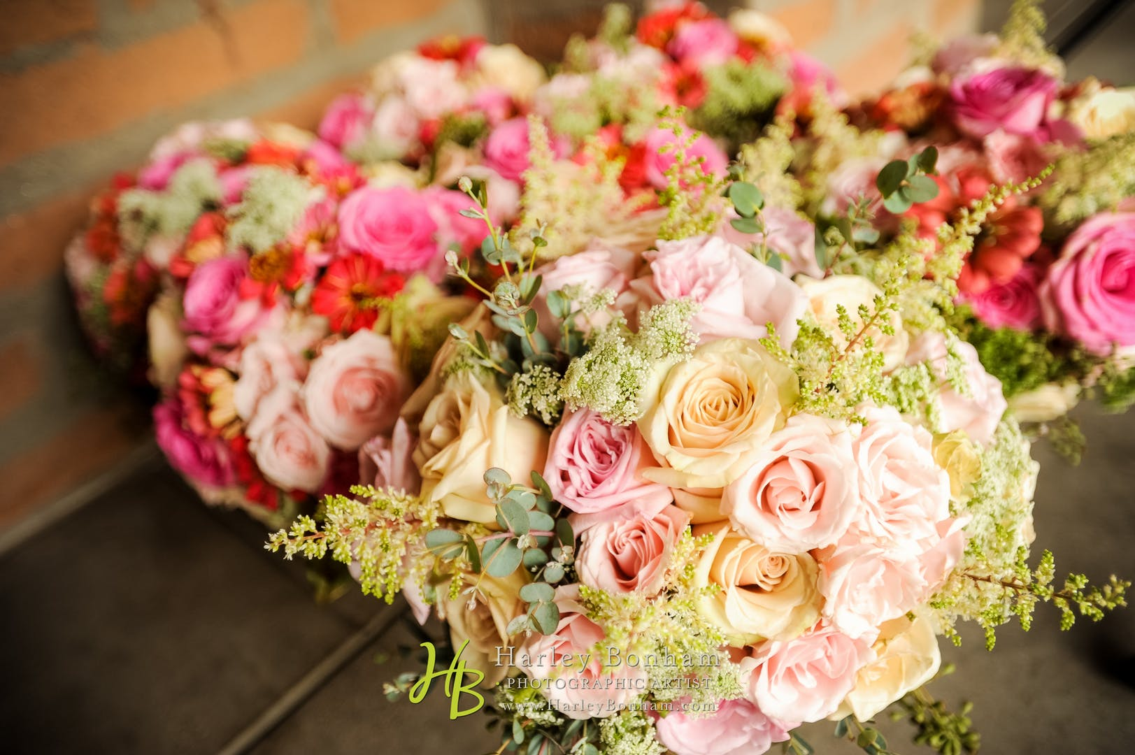 Bouquets of pink and yellow roses, splashed with sprigs of greenery.