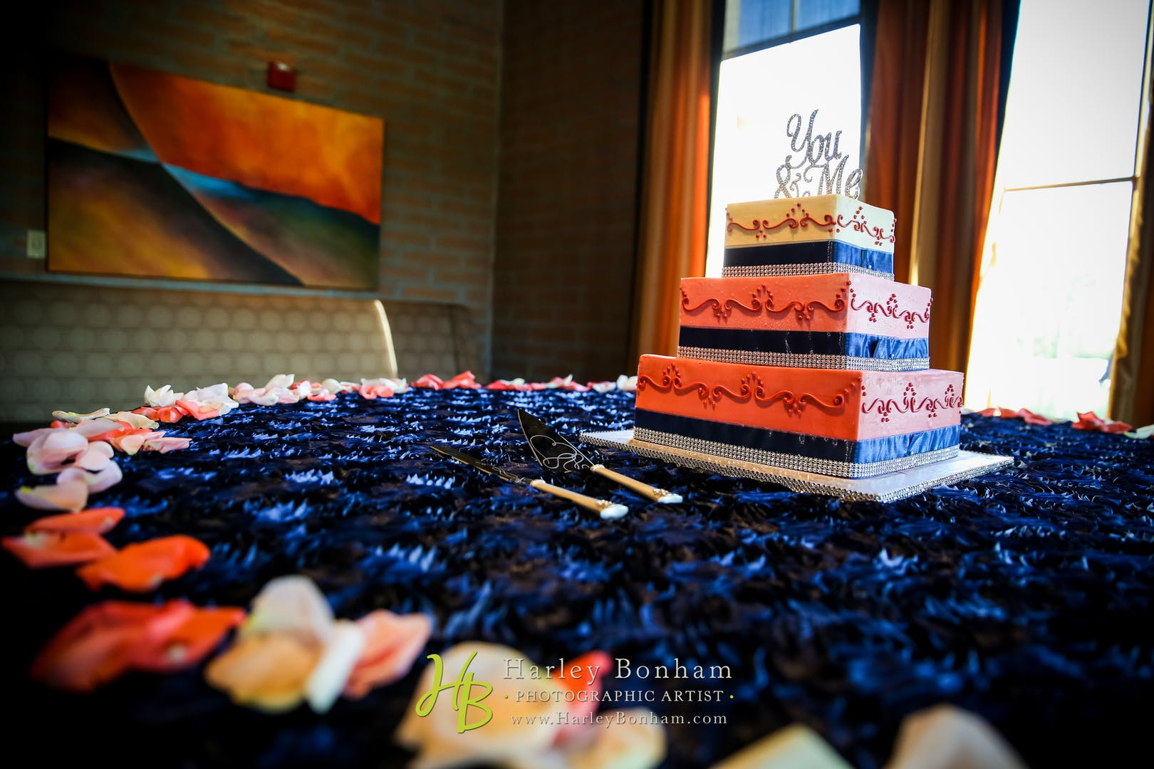 Rose and white wedding cake atop a table adorned with a deep blue cloth and lined with rose petals.