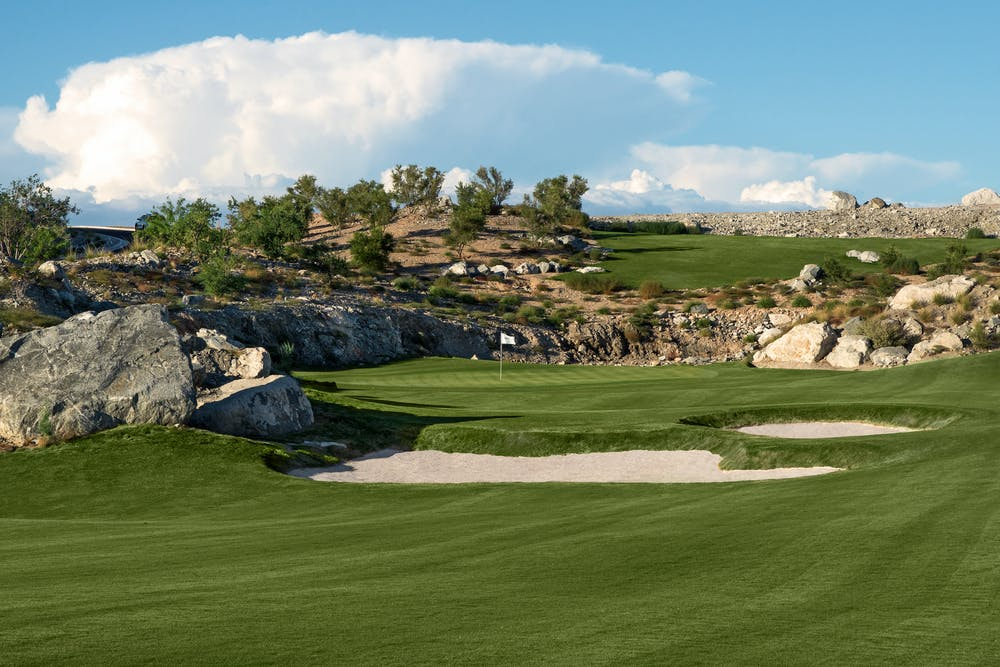 Pretty photo of green fairway, fairway bunkers, and beautiful clouds in the background.