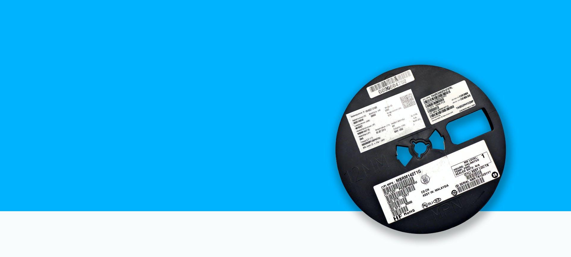 Eine SMD-Spule mit vielen Etiketten und Codes vor blauem Hintergrund