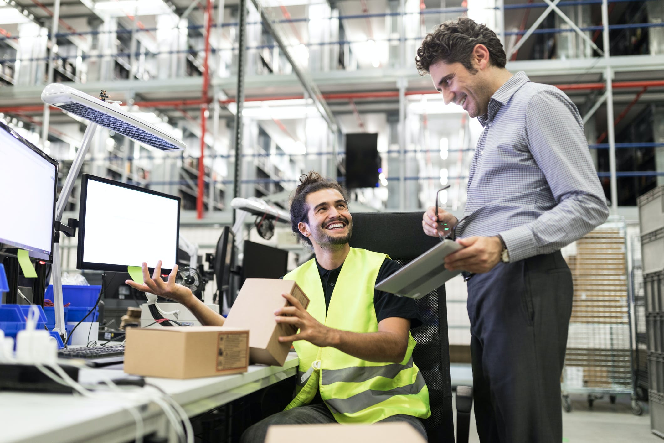Employé épanoui aux côtés de son supérieur dans un entrepôt automatisé.