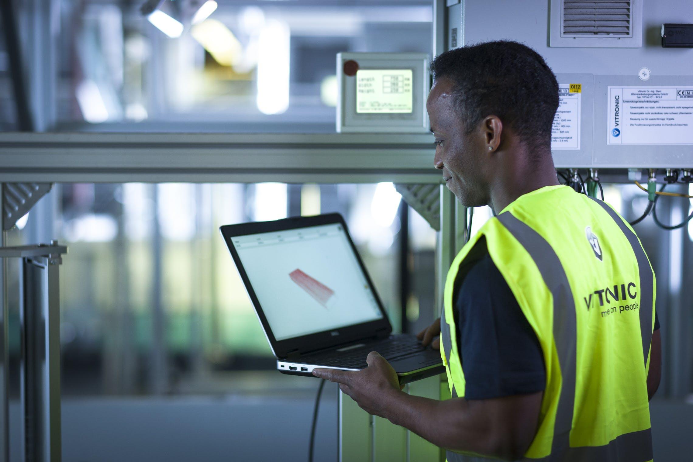 Ein Arbeiter mit Notebook bei der Datenanalyse