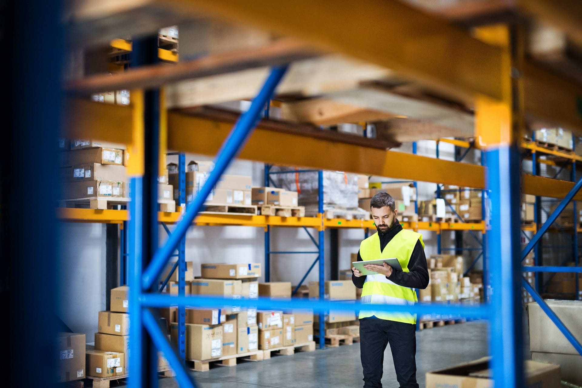 An employee in a yellow safety vest in a high-bay warehouse