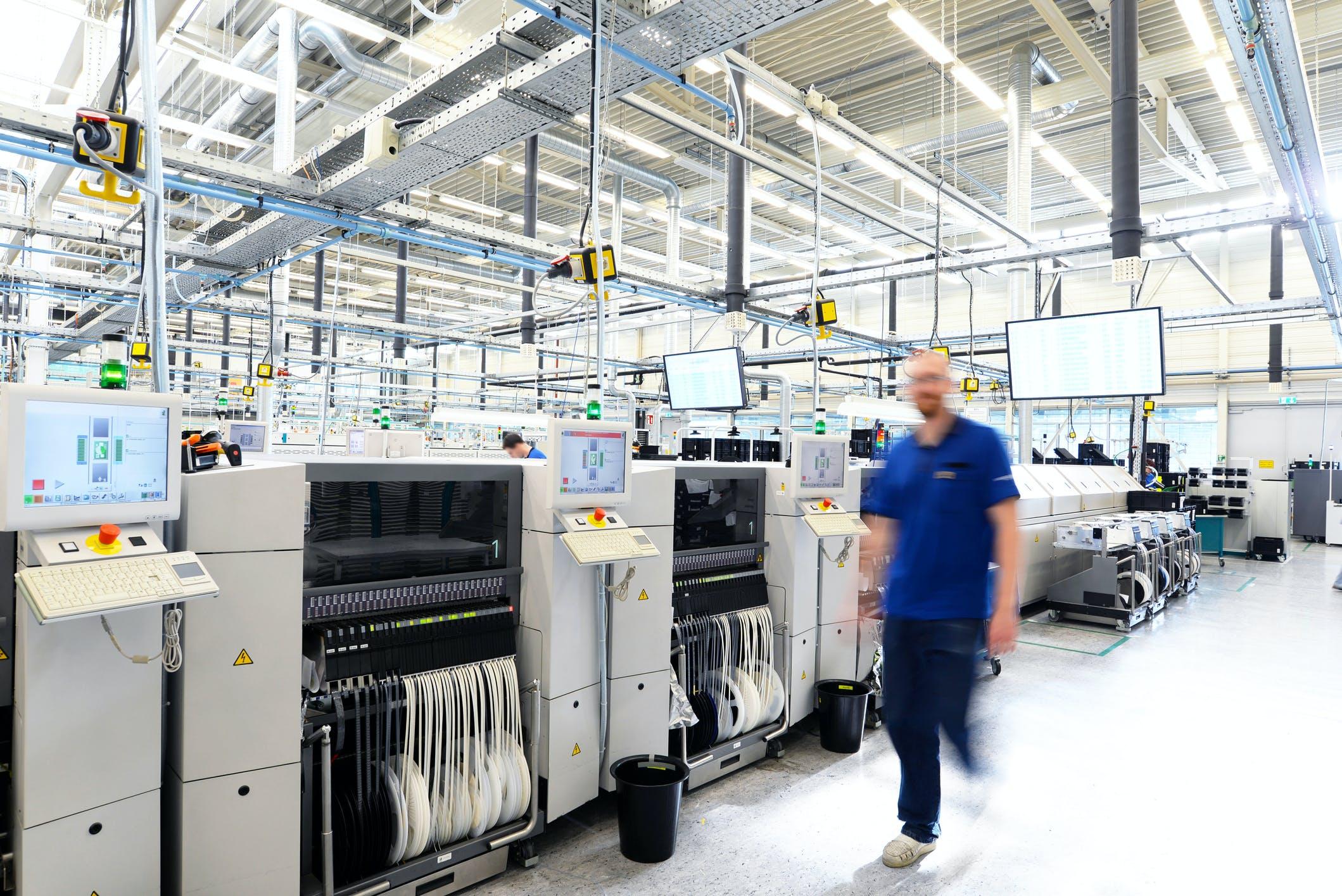 Ein Mitarbeiter läuft durch eine Werkhalle mit SMD-Spulen.