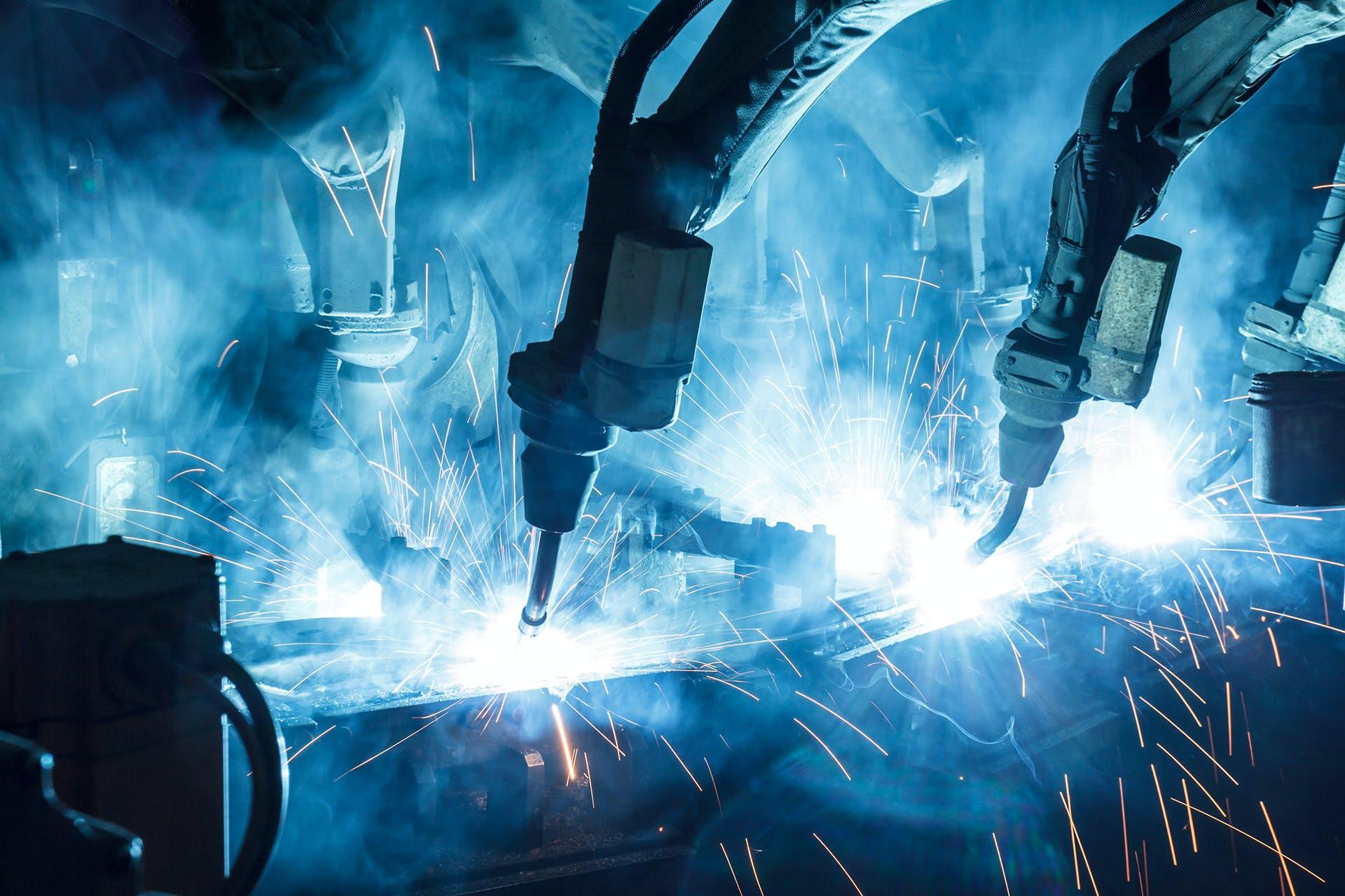 Blick in die Produktion mit schweißenden Roboterarmen und Funken, im Hintergrund ein Arbeiter.
