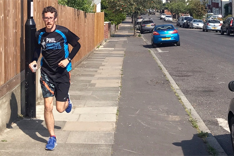 Man wearing a Prostate Cancer UK shirt running on road in the sunshine