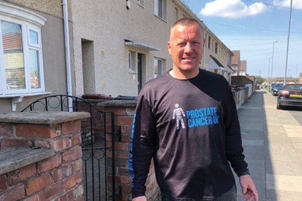 Man wearing a Prostate Cancer UK t-shirt, smiling outside