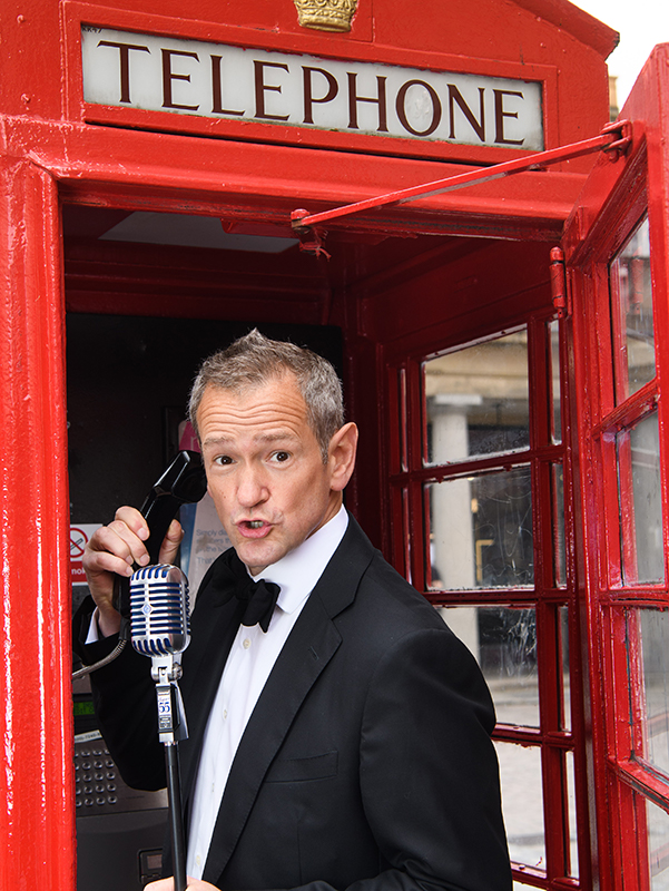 Alexander Armstrong singing in a telephone box