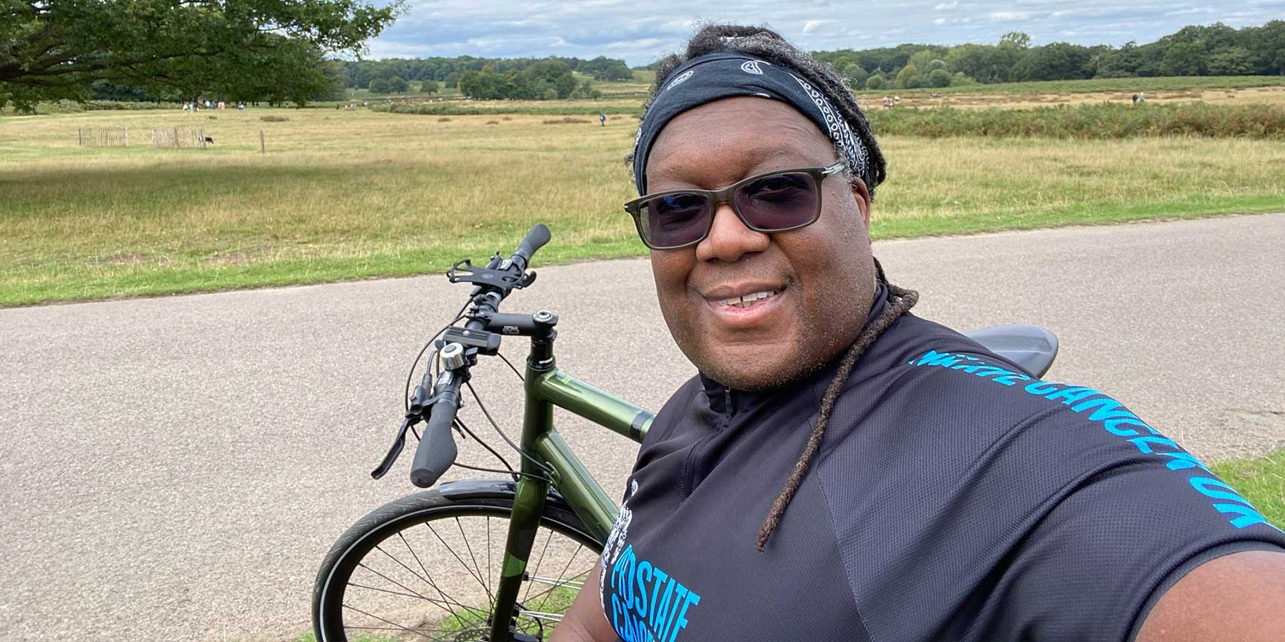 Man smiling taking a selfie in his cycling jersey with his bike in a field