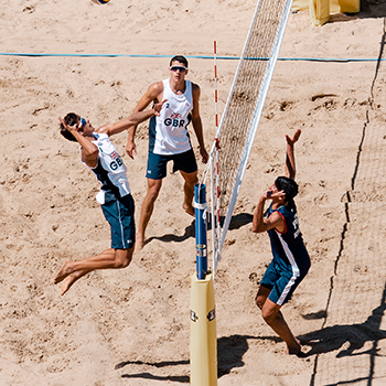 3 men playing beach volleyball