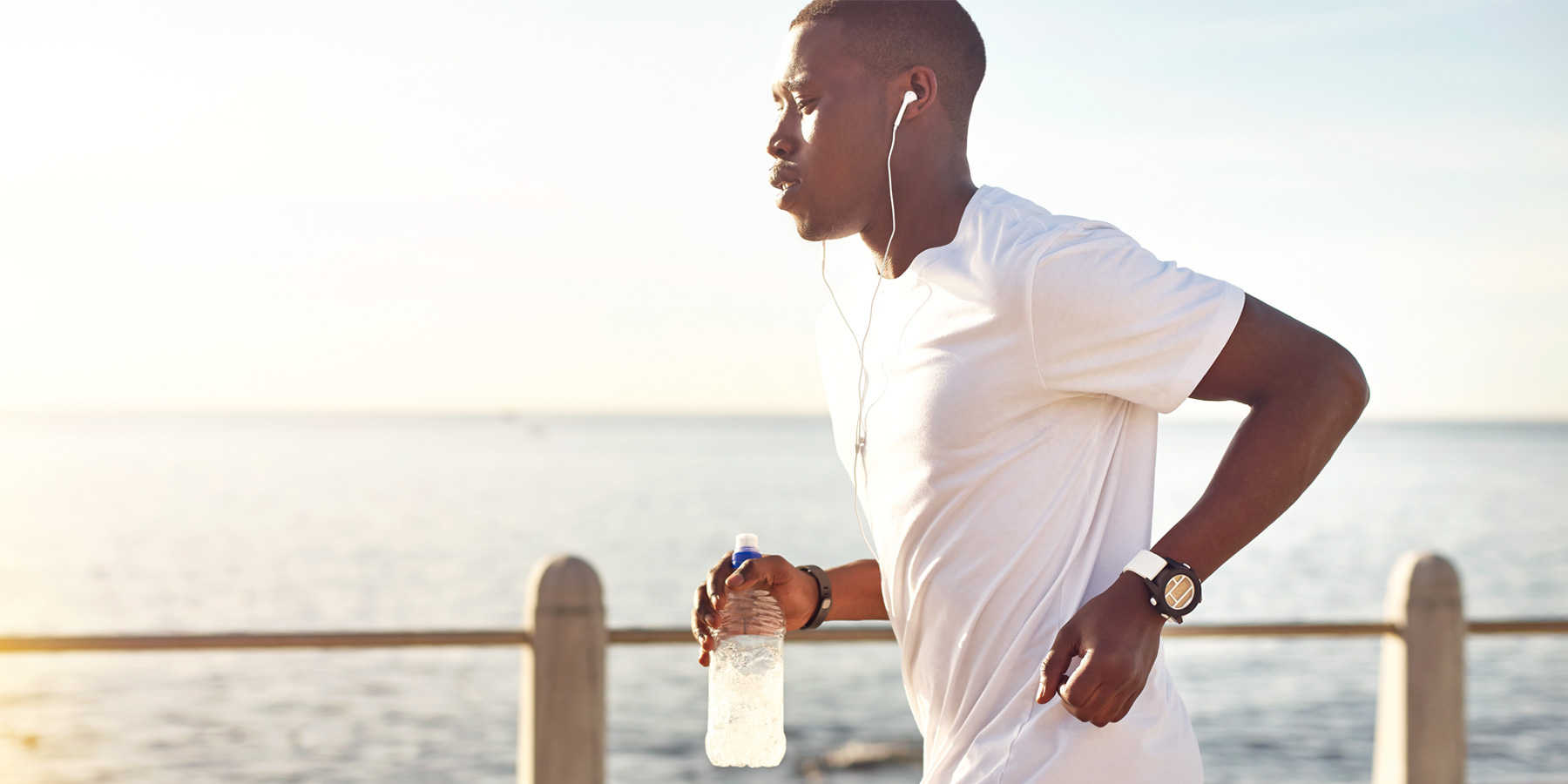 Man running in the evening by the sea, wearing headphones and holding a drink bottle