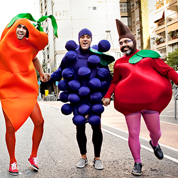 3 men in fancy dress. 1 man dress as a bright orange carrot, 1 as a purple raspberry and 1 dress as a bright red strawberry.