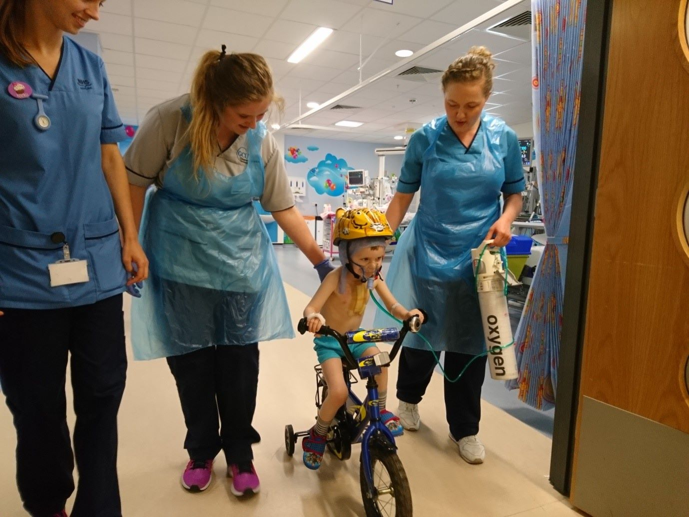 Nurses helping a young child to ride their bike in a hospital