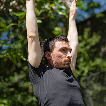 Man with arms up in the air doing Burpees