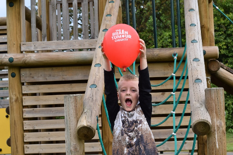 Boy covered in mud on a climbing frame holding up a  The Brain Tumour charity red balloon