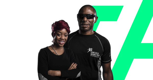 Two people in The Dame Kelly Holmes Trust tops smiling towards the camera on a transparent background.