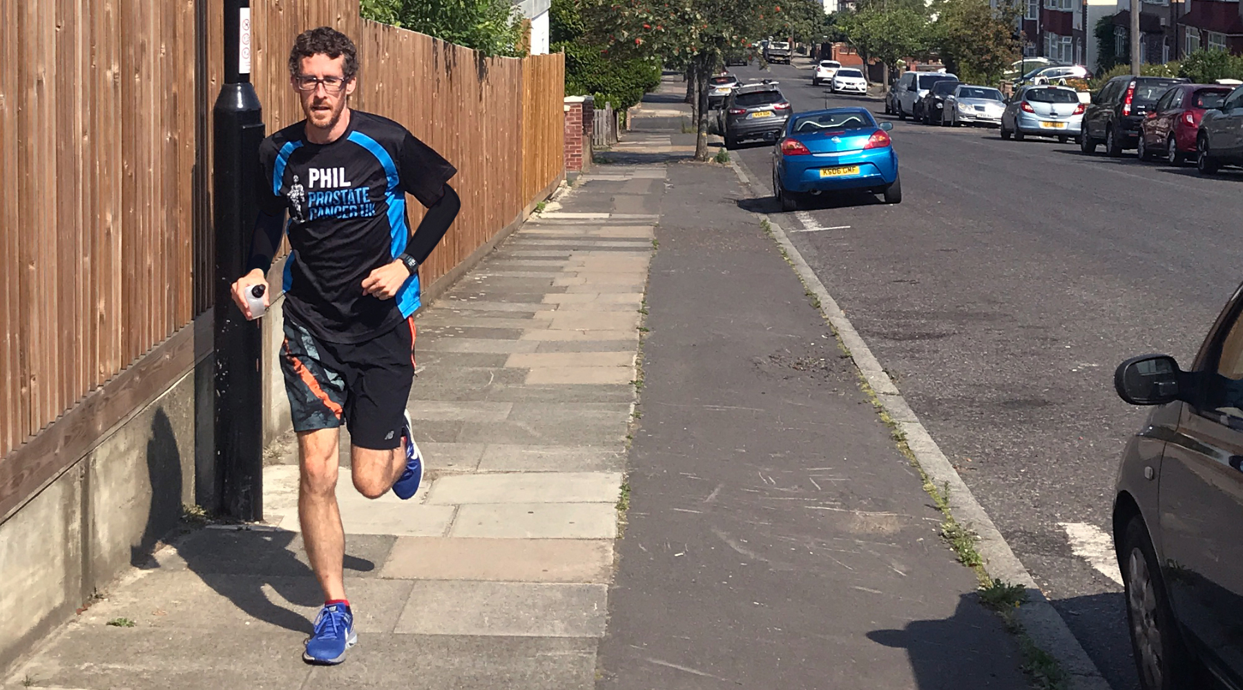 Man running along the street in a Prostate Cancer UK running top