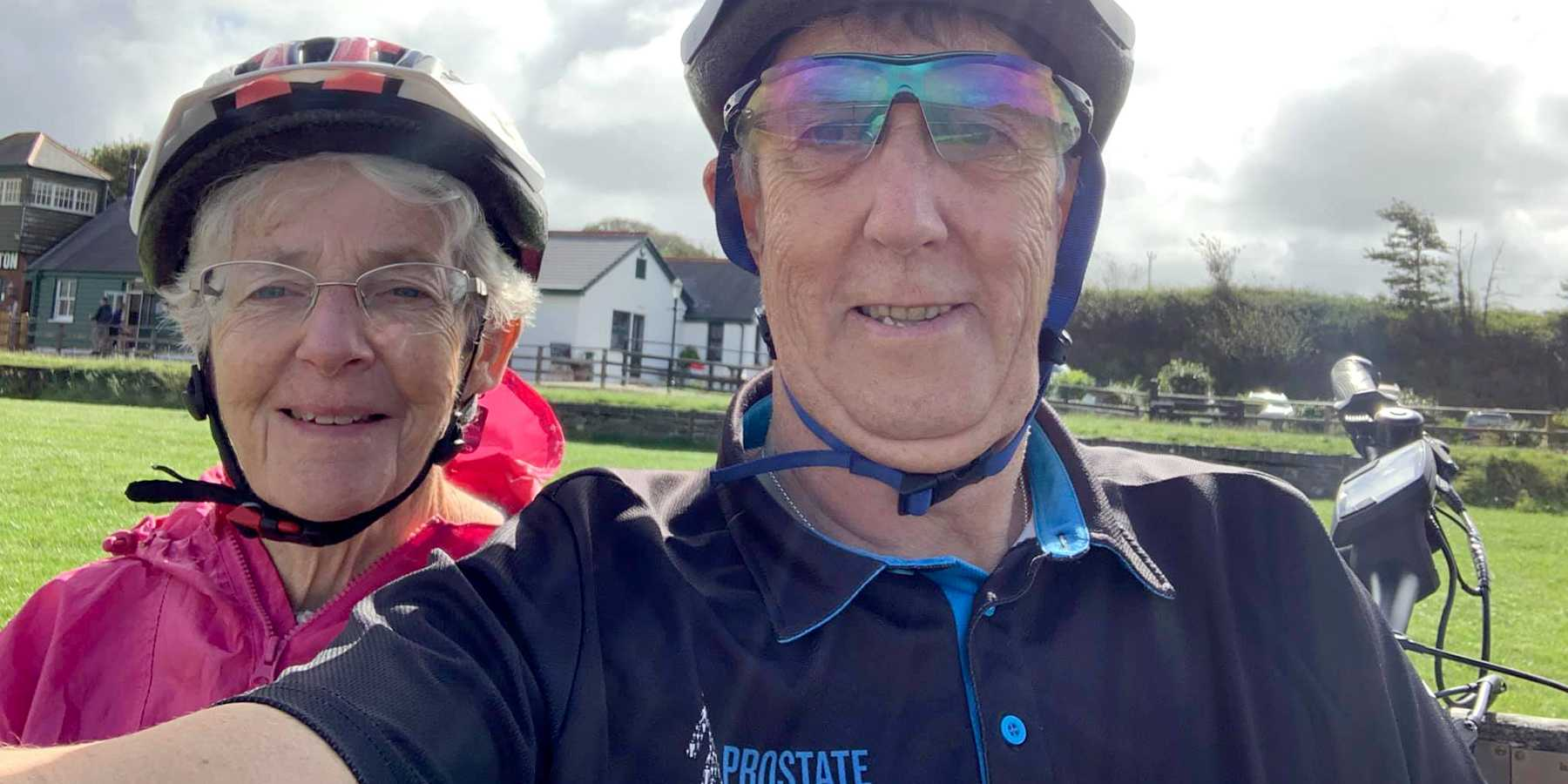 Picture of a man and a woman in cycling outfits, smiling towards the camera outside