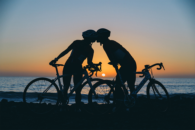 The silhouettes of two cyclists at sunset, kissing.