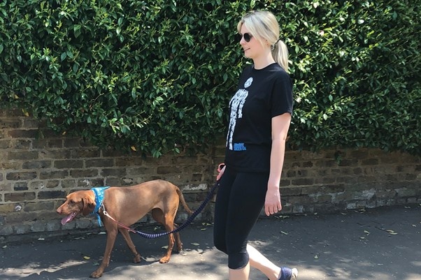 Woman in Prostate Cancer UK t-shirt walking a dog outside