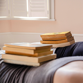 Two people in the plank position with books on their backs