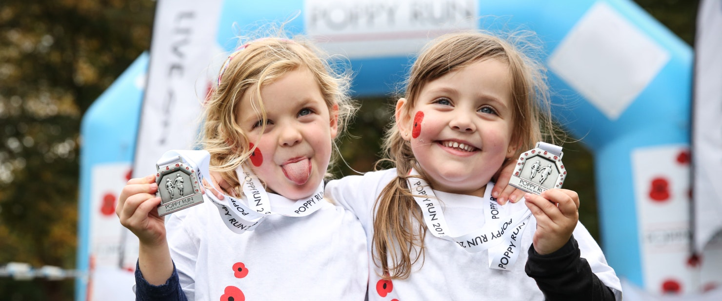 Two young girls holding Poppy Run medals.  The girl on the left is sticking out her tongue whilst the girl on the right is smiling.