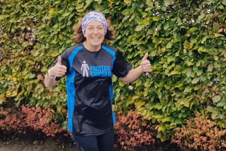 Image of a woman running in Prostate CanceR UK T-shirt smiling with her thumbs up to the camera