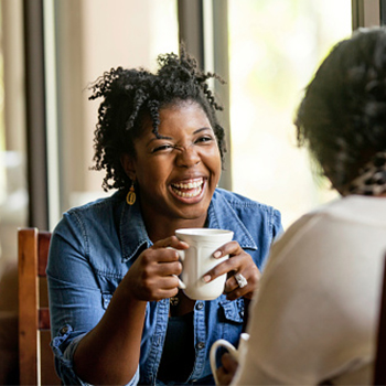 Woman laughing holding mug talking to another person.