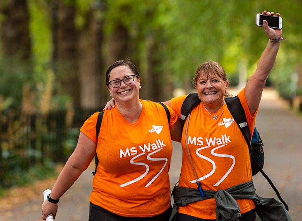 Two women wearing orange t-shirts walking.