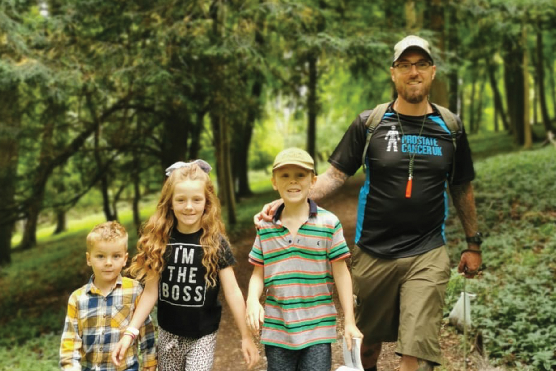 A man and three children walking through the woods.