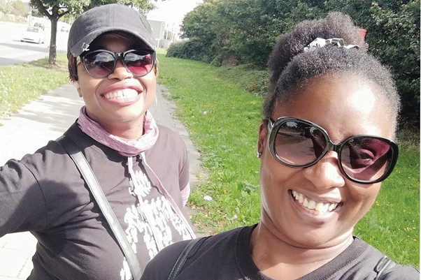 Two women wearing Prostate Cancer UK t-shirts, smiling towards the camer