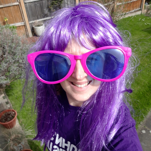 A woman dressed up in a purple wig and big pink sunglasses.