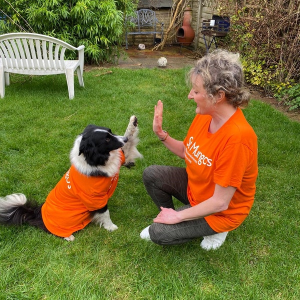 Image of a woman high fiving her dog, both in St Mungo's t-shirt