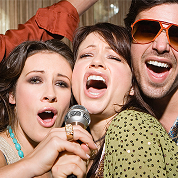2 women holding and singing into a microphone with another man singing in sun glasses