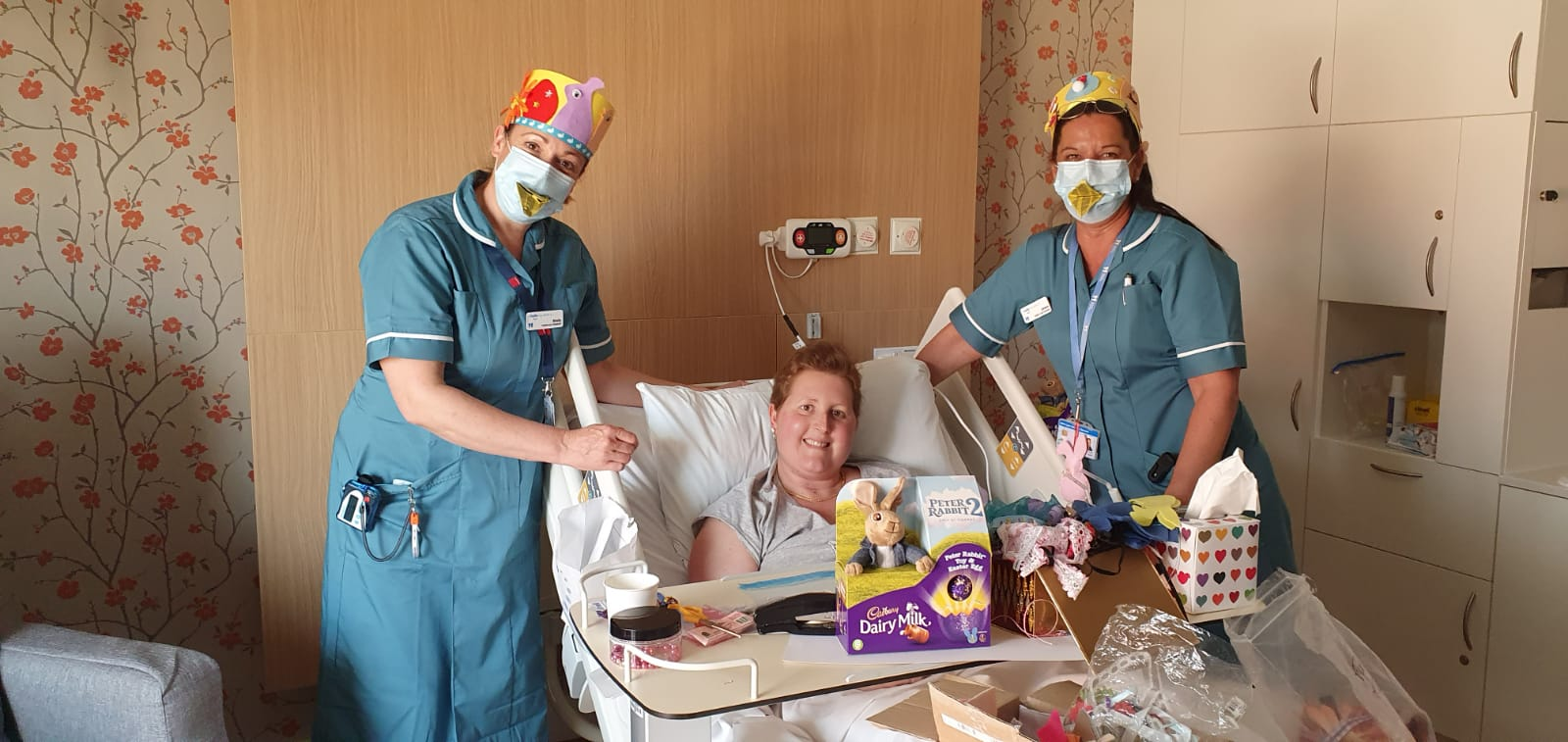 Amanda in a hospital bed with 2 nurses and an Easter Egg
