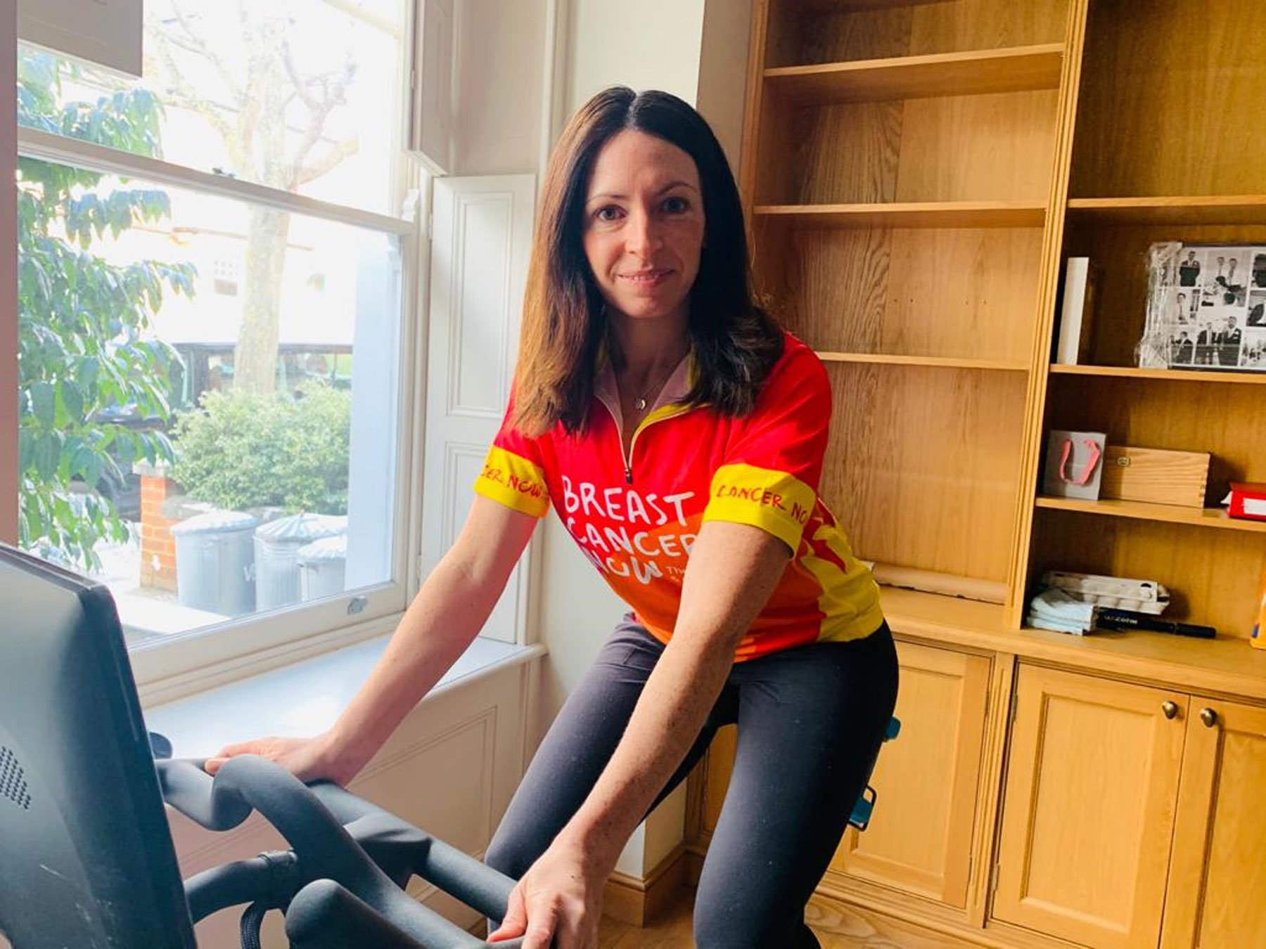 Image of a woman cycling indoors at home