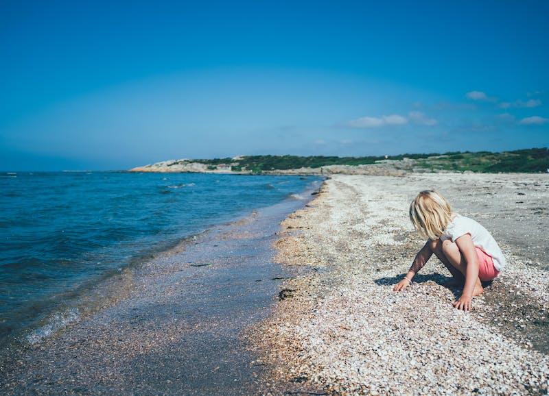 Ett barn sitter och leker med snäckorna vid vattenbrynet
